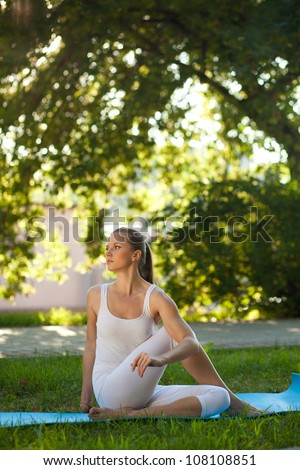 Beautiful young woman practices yoga in nature; sitting on carre-mat, twisted spine, holding her knee hand - stock photo