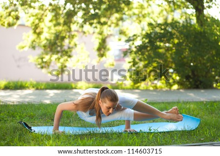 Beautiful young woman practices yoga in nature; standing on the hands, knee lying on the shoulder - stock photo