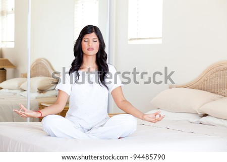 beautiful young woman practicing yoga meditation on her bed - stock photo