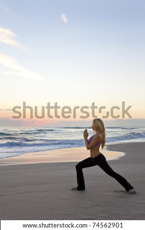 Beautiful young woman practicing yoga on a beach at sunrise or sunset - stock photo