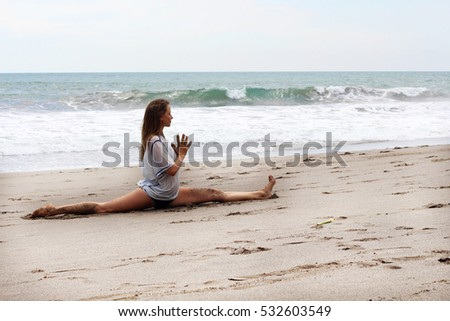 Beautiful young woman practicing yoga on a beach in Bali