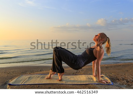 Beautiful young woman practicing yoga on mat outdoors at river bank on sand at sunset, horizontal view