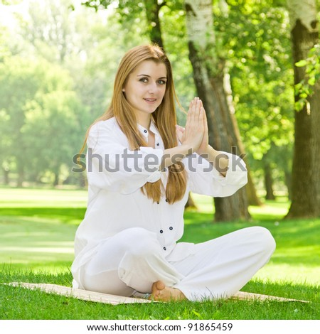 Beautiful young woman practicing yoga outdoors.