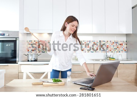 Beautiful young woman preparing lunch at the kitchen - stock photo