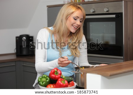 Beautiful young woman preparing supper standing at the stove in the kitchen stirring ingredients in a large stainless steel pot - stock photo