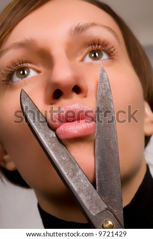Beautiful young woman pretending to cut her lips with scissors