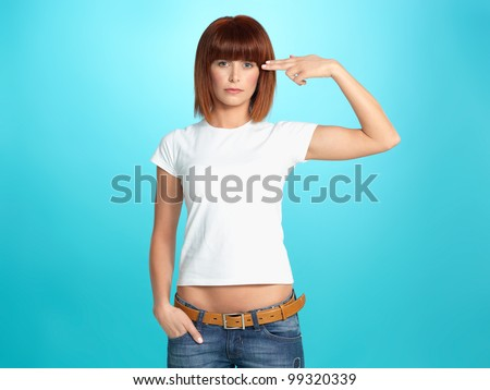 beautiful, young woman pretending to shoot a gun at her head, on blue background