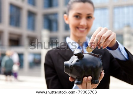 beautiful young woman putting a coin into a big pink piggy bank in front her office building (focus on the piggy bank) - stock photo