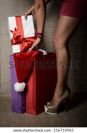 Beautiful young woman putting gift box in colored shopping bags, long legs on high heels closeup over canvas background, glamour holiday shopping concept, image toned  - stock photo