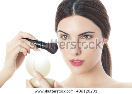 Beautiful young woman putting makeup, isolated on white - stock photo