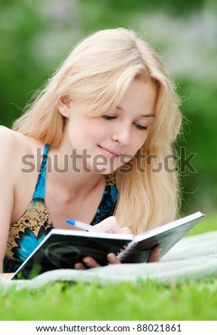 Beautiful young woman read book, at green summer park