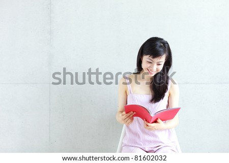 Beautiful young woman reading a book - stock photo