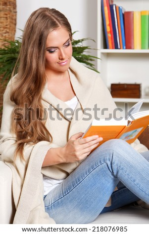 Beautiful young woman reading a book at home