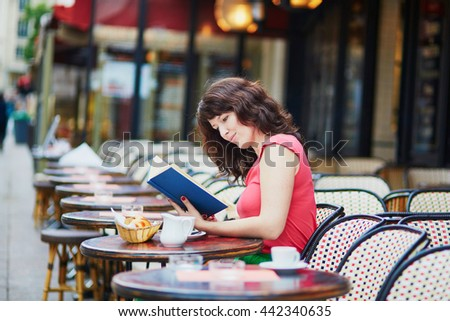 Beautiful young woman reading a book in traditional Parisian outdoor cafe, Paris, France
