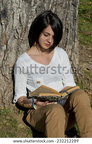 Beautiful young woman reading a book outside in park - stock photo