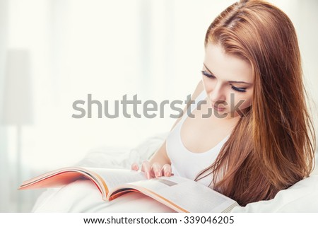 Beautiful young woman reading a magazine and lying on the bed at home