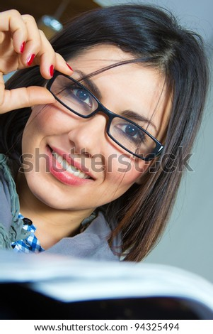 beautiful young woman reading a magazine on the sofa - stock photo