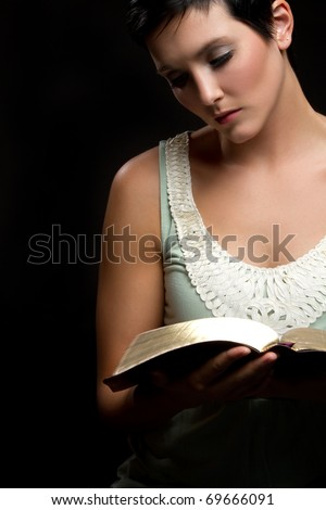 Beautiful young woman reading bible - stock photo