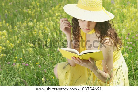 beautiful young woman reading book in a field full of yellow flowers