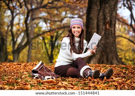 beautiful young  woman reading book in autumn park - stock photo