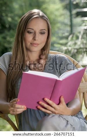 Beautiful young woman reading book in park - stock photo