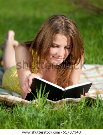 Beautiful young woman reading book outdoor on green grass - stock photo