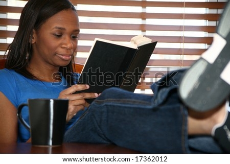 Beautiful young woman reading book with coffee. - stock photo
