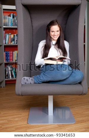 Beautiful young woman reading in library