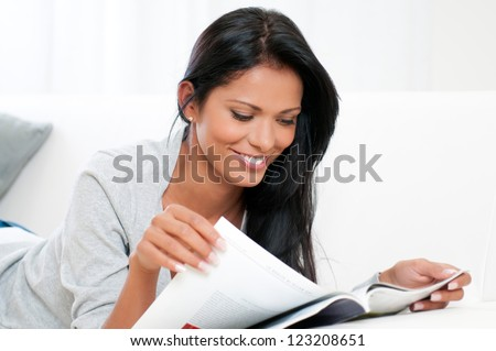 Beautiful young woman reading magazine and lying on sofa at home - stock photo