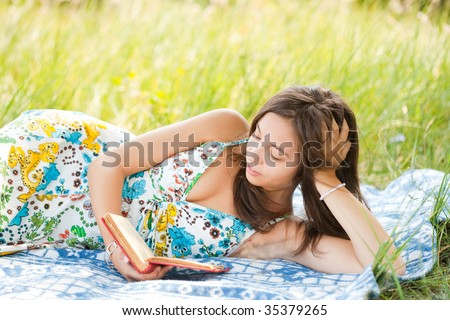 Beautiful young woman reading outdoor, lying on a blanket - stock photo
