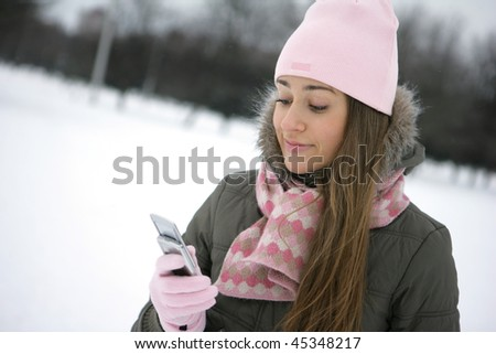 Beautiful young woman reading sms on her cellular phone - stock photo
