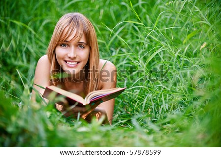 Beautiful young woman reads book, on green summer background. - stock photo