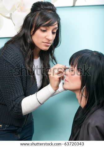 Beautiful young woman receives beauty treatment from attractive Indian beautician - stock photo
