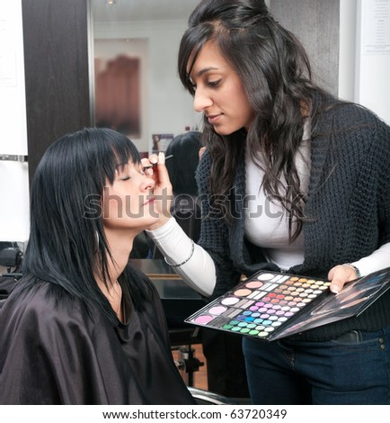Beautiful young woman receives beauty treatment from attractive Indian beautician. - stock photo