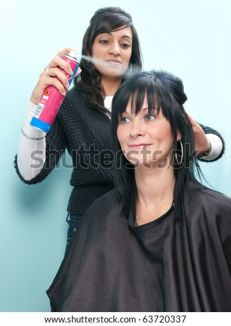 Beautiful young woman receives hairspray from attractive Indian hair stylist - stock photo