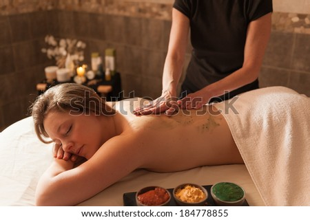 Beautiful young woman receiving a massage in a spa. - stock photo