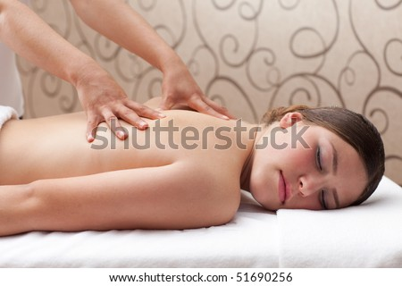 Beautiful young woman receiving back massage in spa, shallow depth of field, focus on first hand