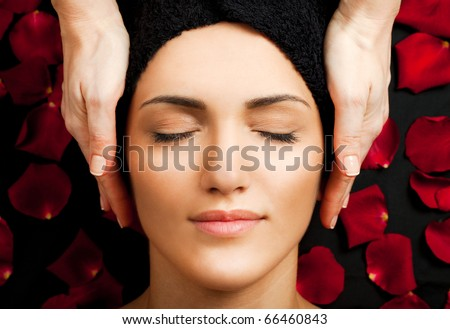 Beautiful young woman receiving face massage at spa - stock photo