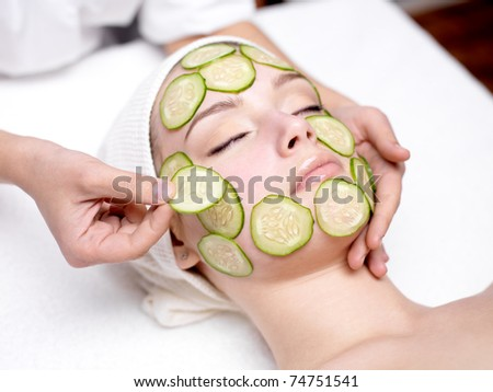 Beautiful young woman receiving facial mask of cucumber in beauty salon - indoors - stock photo