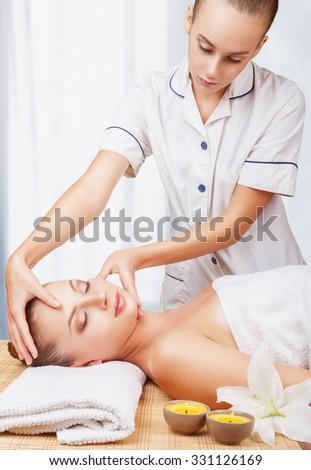Beautiful young woman receiving facial massage in the spa salon - stock photo
