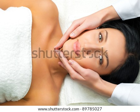 Beautiful young woman receiving facial massage looking at camera in a spa center - stock photo