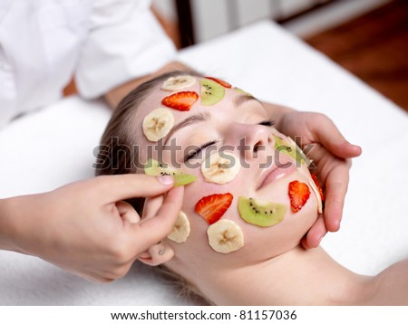 Beautiful young woman receiving fruit mask on a face in beauty salon - indoors - stock photo