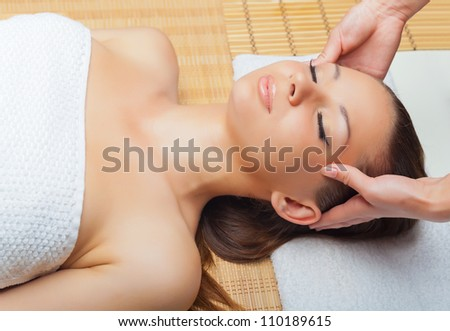 Beautiful young woman receiving massage of head in spa salon - stock photo