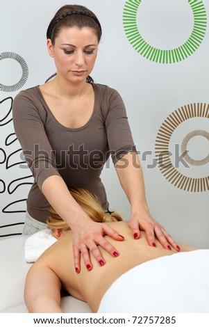 Beautiful young woman receiving professional massage - stock photo