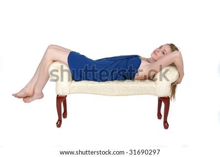 beautiful young woman reclining on white studio bench - stock photo