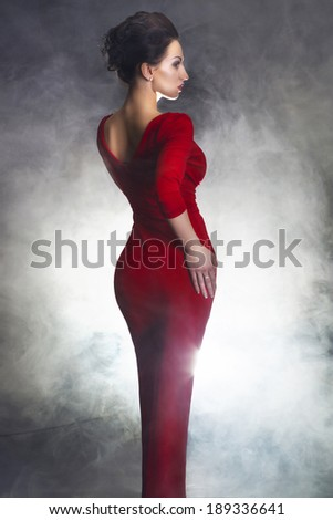 Beautiful young woman red dress studio dark background - stock photo