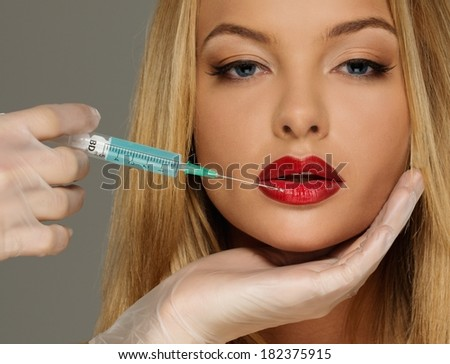 Beautiful young woman red lips with syringe  - stock photo