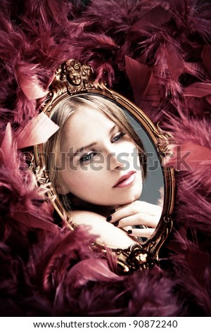 beautiful young woman reflection in mirror surrounded by plumage - stock photo