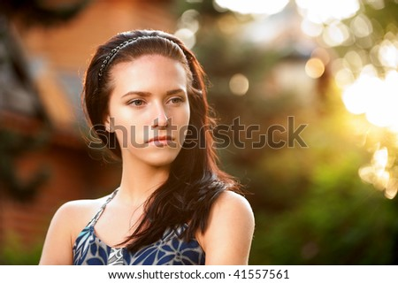 Beautiful young woman reflects on life in summer city park.