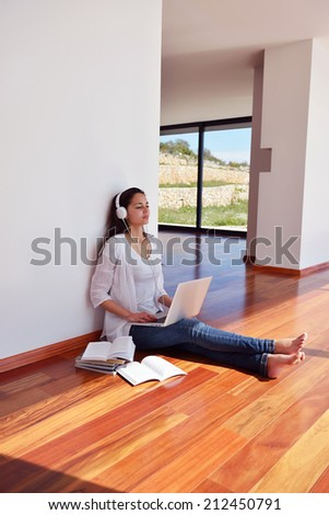 beautiful young woman relax and work on laptop computer while working on laptop computer and read book at home - stock photo